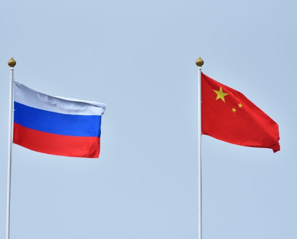 China and Russia flag waving in the wind against white cloudy blue sky together. Diplomacy concept, international relations.