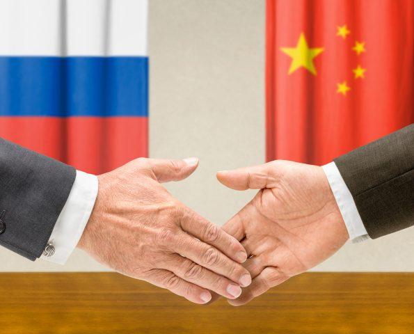 Representatives of Russia and China shake hands