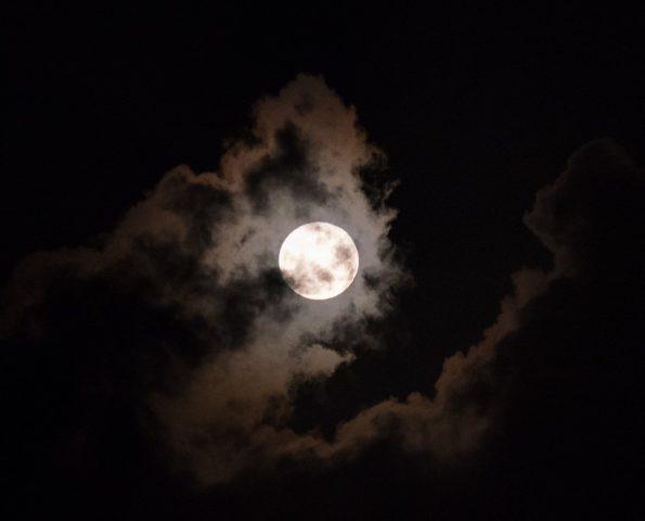 Full moon behind clouds glowing on a dark night sky