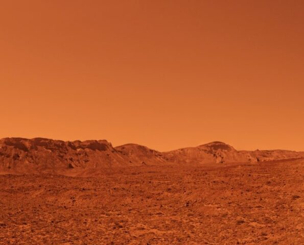 A landscape scene of Mars. It is desert-like and sandy with mountains in the background. The air is hazy and the whole image is tinted red.