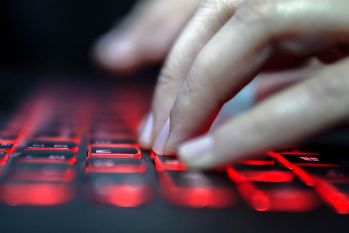 A hand typing at a keyboard that is backlit with red light